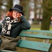 Ivonne Bressers zit op een bank in een park, draagt een hoed enlacht in de camera