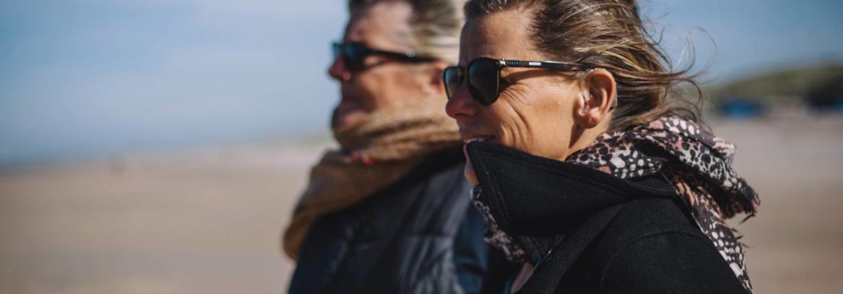 Hetty en Machteld dragen beiden een zonnebril en kijken met de haren in de wind richting de zee