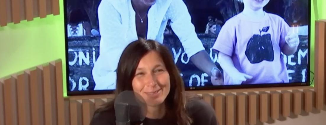 Ushermom, Carolien de Bie zit aan tafel in de studio. Op de achtergrond zie je een beeld van een foto van een lachende kleuter Jackson