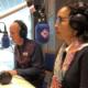 Gracia en George in de studio met ieder een koptelefoon op en zittend voor een grote microfoon
