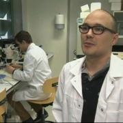 Erwin in een witte jas in zijn lab.