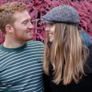 Rens en Joelle kijken elkaar lachend aan. Op de achtergrond zijn paarse bloemetjes te zien.