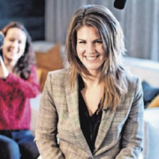 Joyce de Ruiter lacht voluit in de camera van de fotograaf. Achter haar is Lisanne van Spronsen te zien met een grote filmcamera op haar schouder.