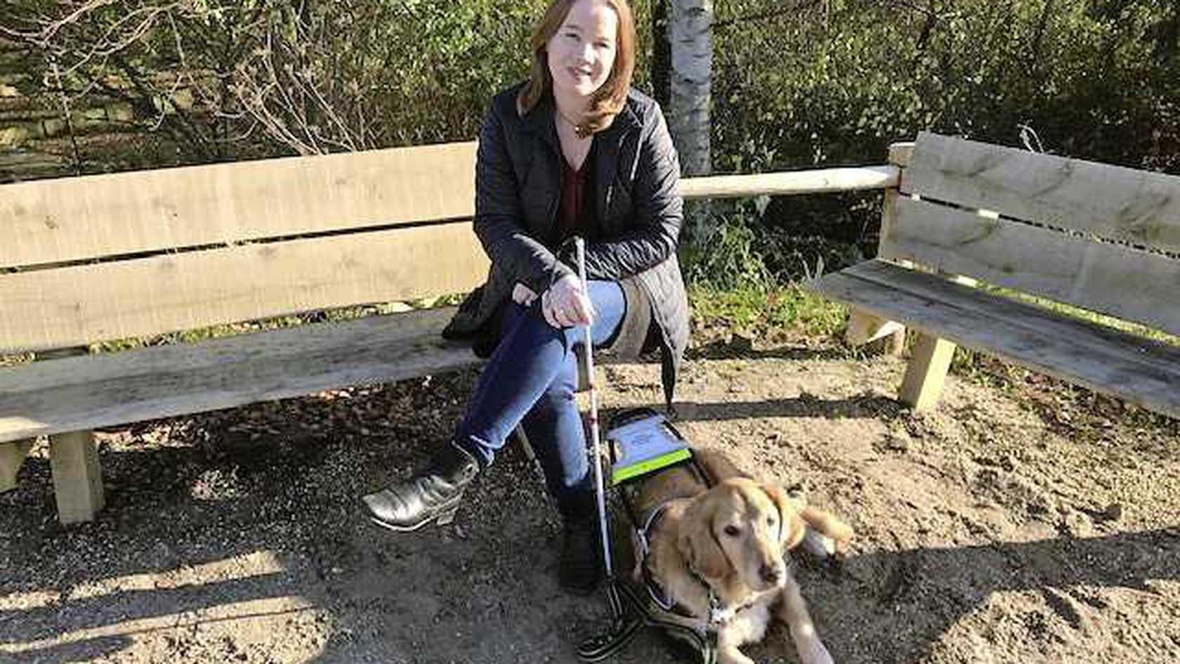 Leonie zit op een bank buiten in het park met haar hond Wouter liggend aan haar voeten