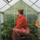 Lotte Klaver zittend in een kas met planten. ze draait haar hoofd naar achteren zodat je haar gezicht niet kan zien. Ze draagt een rood truitje en een rood-oranje broek wat een contrsta geeft met de groene planten op de achtergrond.