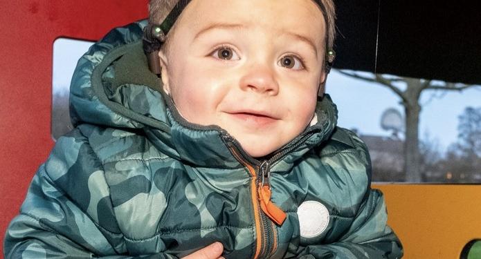 Een lachende peuter die met grote ogen naar de camera kijkt. Hij draagt een warme jas en muts
