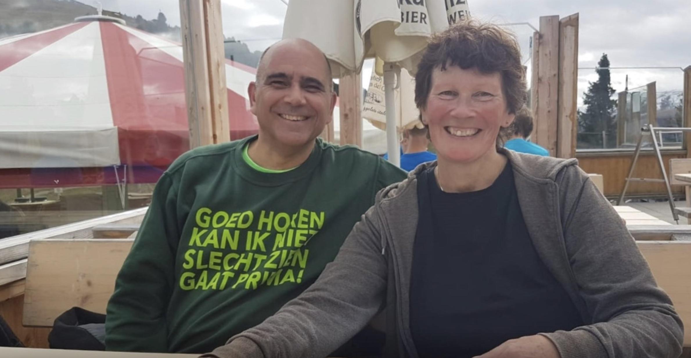 Peter samen met zijn vrouw. Hij draagt een trui met de tekst: Goed horen kan ik niet, slecht zien kan ik prima